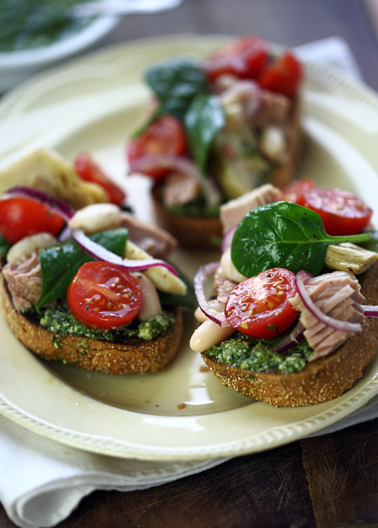 Pesto bruschetta topped with tuna, white beans, cherry tomatoes and artichokes